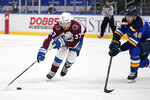 Colorado Avalanche's J.T. Compher (37) handles the puck as St. Louis Blues' Jake Walman (46) defends during the third period of an NHL hockey game Thursday, April 22, 2021, in St. Louis. (AP Photo/Jeff Roberson)