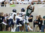 Michigan State's Felton Davis III (18) catches a pass against Utah State's Shaq Bond (25) and Jontrell Rocquemore (3) during the first quarter of an NCAA college football game, Friday, Aug. 31, 2018, in East Lansing, Mich. (AP Photo/Al Goldis)