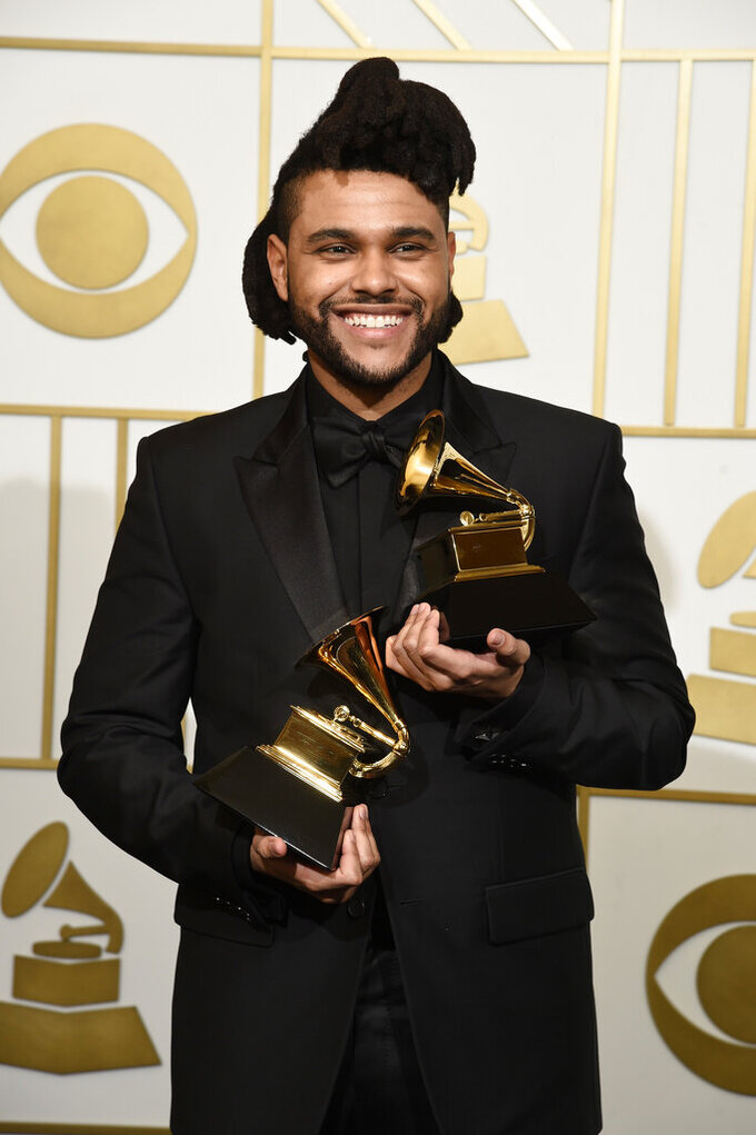 """FILE - The Weeknd poses in the press room with the awards for best R&B performance for """"Earned It (Fifty Shades of Grey)"""" and best urban contemporary album for """"Beauty Behind The Madness"""" at the 58th annual Grammy Awards in Los Angeles on Feb. 15, 2016. The Weeknd had the No. 1 song of 2020 but """"Blinding Lights"""" was not nominated for a Grammy Award. (Photo by Chris Pizzello/Invision/AP, File)"""