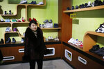 In this Friday, Feb. 1, 2019, photo, a guide stands in a product exhibition room at Ryuwon Shoe Factory that specializes in sports footwear, in Pyongyang, North Korea. North Korean pop culture, long dismissed by critics as a kitschy throwback to the dark days of Stalinism, is getting a major upgrade under leader Kim Jong Un. The changes are being seen in everything from television dramas and animation programs to the variety and packaging of consumer goods, which have improved significantly under Kim. (AP Photo/Dita Alangkara)