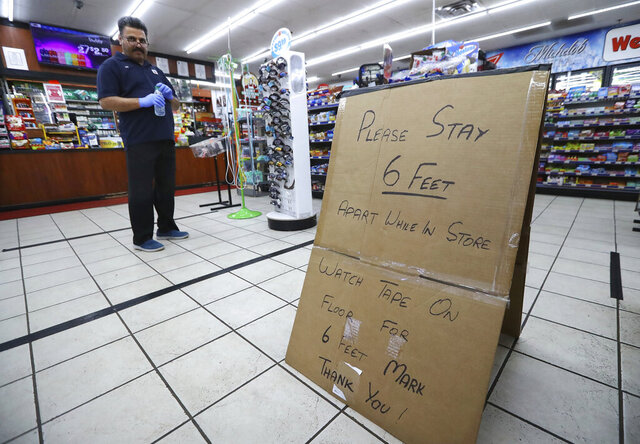 Ejaz Tarar stands next to his makeshift sign keeping customers six feet apart while cleaning the inside of the Food Mart in Newton County on Thursday, March 26, 2020, in Newborn. The store laid down tape to mark six foot barriers for customers. (Curtis Compton/Atlanta Journal-Constitution via AP)
