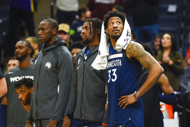 Minnesota Timberwolves forward Robert Covington, right, checks the scoreboard in the final seconds of overtime against the Sacramento Kings as Timberwolves center Gorgui Dieng, left, and Timberwolves center Naz Reid, center look on during an NBA basketball game Monday, Jan. 27, 2020, in Minneapolis. The Kings won 133-129 in overtime. (AP Photo/Craig Lassig)