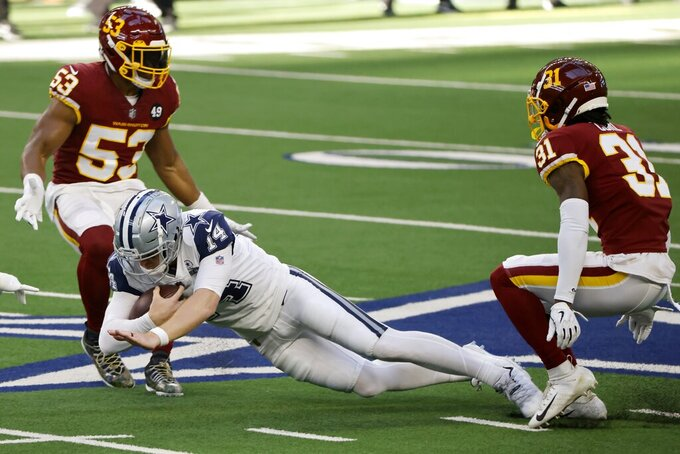 Dallas Cowboys quarterback Andy Dalton (14) dives forward for extra yardage between Washington Football Team linebacker Jon Bostic (53) and safety Kamren Curl (31) after carrying the ball in the first half of an NFL football game in Arlington, Texas, Thursday, Nov. 26, 2020. (AP Photo/Ron Jenkins)
