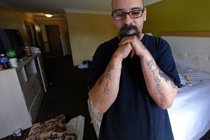 """David Moran poses in his hotel room, paid for by a pandemic voucher program, at the Hilltop Inn in Berlin, Vt., Wednesday, June 16, 2021. Tens of thousands of homeless like Moran, who now has a job at Applebee's, have been staying in hotels across the U.S. paid for by federal programs aimed at preventing the spread of COVID-19. """"I'm not going to be able to get a shower on a regular basis, which around food is not a good thing,"""" he said. """"So I think there should be more available funds for people that are really trying."""" (AP Photo/Charles Krupa)"""