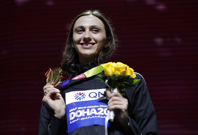 FILE - In this Tuesday, Oct. 1, 2019 file photo, Gold medalist Mariya Lasitskene, who participates as a neutral athlete, poses during the medal ceremony for the women's high jump at the World Athletics Championships in Doha, Qatar. Three-time world high jump champion Mariya Lasitskene has assailed Russian track leaders after they were charged with using fake medical documents during an investigation. Lasitskene has called for swift and radical reforms and the removal of officials appointed by track federation president Dmitry Shlyakhtin. (AP Photo/Nariman El-Mofty, File)
