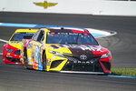 Kyle Busch (18) drives through a turn during practice for the NASCAR Cup Series auto race at Indianapolis Motor Speedway in Indianapolis, Saturday, Aug. 14, 2021. (AP Photo/Michael Conroy)