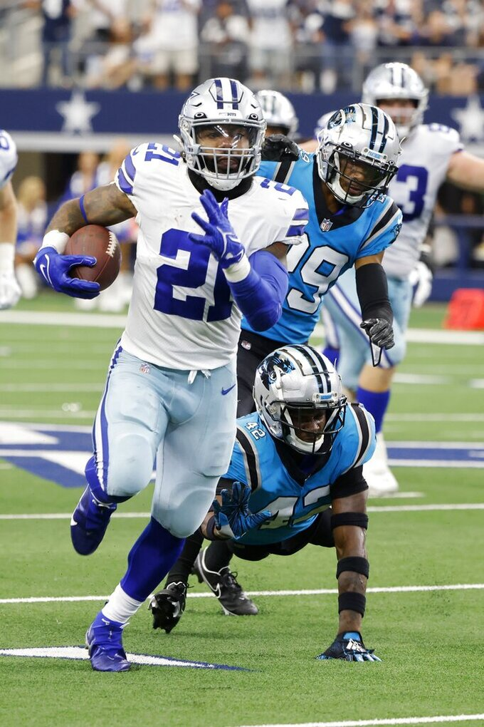 Dallas Cowboys running back Ezekiel Elliott (21) runs the ball after getting past Carolina Panthers safety Sam Franklin (42) in the second half of an NFL football game in Arlington, Texas, Sunday, Oct. 3, 2021. (AP Photo/Michael Ainsworth)