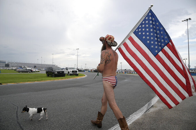 Tony Pacetti walks around the infield with a United States flag before a NASCAR Cup Series auto race at Daytona International Speedway, Saturday, July 6, 2019, in Daytona Beach, Fla. (AP Photo/Phelan M. Ebenhack)