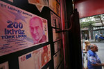 FILE-In this Friday, Aug. 17, 2018 file photo, an oversized copy of a 200 Turkish lira banknote, featuring a photo of modern Turkey's founder Mustafa Kemal Ataturk decorates a currency exchange shop in Istanbul. Turkey's currency dropped to an all-time low against the dollar on Thursday Aug. 6, 2020, as the global recession created by the coronavirus pandemic brings to the fore weaknesses in the country's economy.(AP Photo/Lefteris Pitarakis, File)