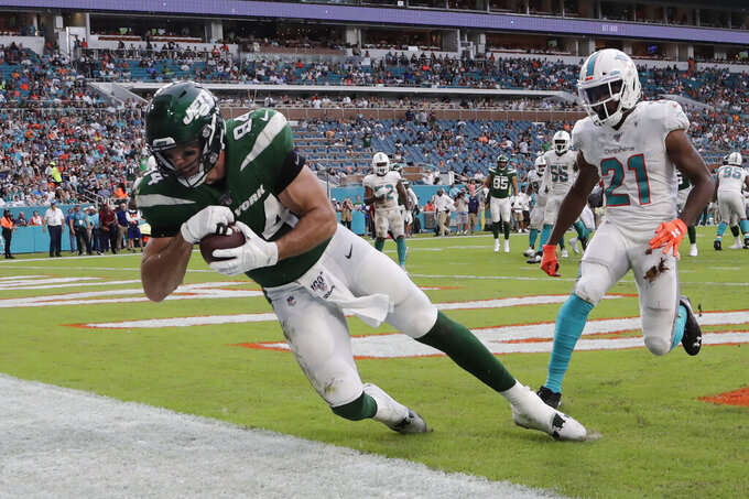 New York Jets tight end Ryan Griffin (84) scores a touchdown against Miami Dolphins cornerback Eric Rowe (21) during the first half of an NFL football game, Sunday, Nov. 3, 2019, in Miami Gardens, Fla. The touchdown was later overturned upon review of the play. (AP Photo/Lynne Sladky)