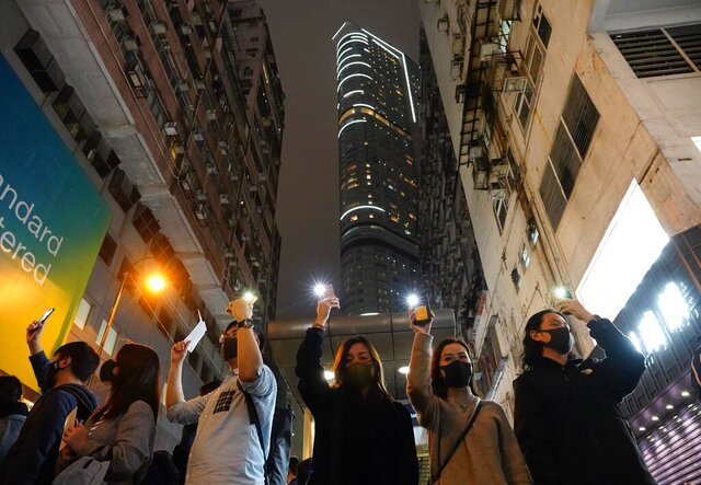 """People raise their cellphones lights as they form a human chain on New Year's eve in Hong Kong, Tuesday, Dec. 31, 2019. Months of pro-democracy protests have brought """"sadness, anxiety, disappointment and even rage,"""" the city's leader Carrie Lam said in a News Year's address Tuesday. Protests that began in June over a proposed extradition law have spread to include demands for more democracy and other grievances. (AP Photo/Vincent Yu)"""