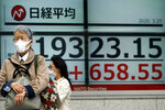 A woman walks past an electronic stock board showing Japan's Nikkei 225 index at a securities firm in Tokyo Friday, March 27, 2020. Shares are mostly higher in Asia after stocks surged again on Wall Street with the approaching approval of a massive coronavirus relief bill by Congress.(AP Photo/Eugene Hoshiko)