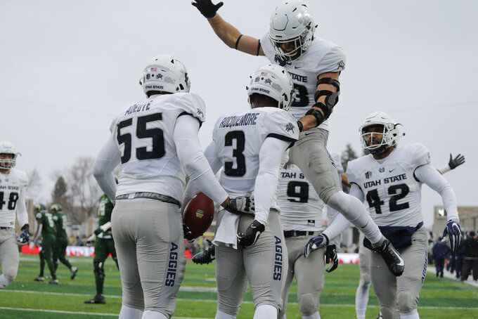 Utah State safety Jontrell Rocquemore (3) is congratulated by teammates Gaje Ferguson (23) and Adewale Adeoye (55) after running an interception back for a touchdown against Colorado State during the second half of an NCAA football game Saturday, Nov. 17, 2018, in Fort Collins, Colo. Utah State won, 29-24. (AP Photo/Jack Dempsey)
