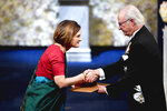 Esther Duflo of France, left, receives the Sveriges Riksbank Prize in Economic Sciences in Memory of Alfred Nobel from King Carl Gustaf of Sweden, during the Nobel Prize award ceremony, at the Stockholm Concert Hall, in Stockholm, Monday, Dec. 10, 2019. (Henrik Montgomery / TT News Agency, Pool via AP)