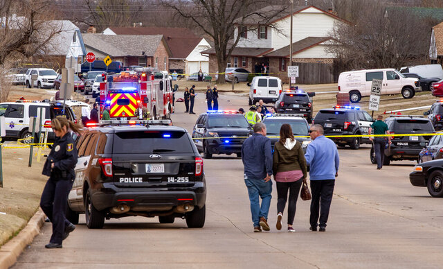 Emergency crews respond to a scene where a vehicle hit several Moore High School students, killing at least one, in Moore, Okla., Monday, Feb. 3, 2020. At least one girl was killed and several other people were injured, three critically, when a motorist slammed his vehicle into the high school cross-country team as they ran along a street outside their suburban Oklahoma City school Monday, officials said. (Chris Landsberger/The Oklahoman via AP)