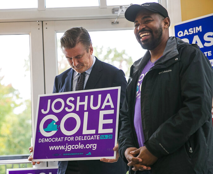 Actor Alec Baldwin holds a Josh Cole campaign sign after accidentally knocking it off a window during a visit to the Leeland Station Clubhouse in Stafford County, Va., on Tuesday, Oct. 22, 2019. Cole, right, who is running for the Virginia House of Delegates 28th District, reacts to the situation. (Peter Cihelka/The Free Lance-Star via AP)
