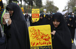 Demonstrators hold anti-U.S. placards in Arabic reading; during an annual rally in front of the former U.S. Embassy in Tehran, Iran, Monday, Nov. 4, 2019. Reviving decades-old cries of