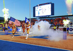 Boise State offensive lineman John Molchon (77) carries a United States flag and safety Evan Tyler (5) carries  a Bleed Blue flag as they lead the team onto the field before an NCAA college football game against Colorado State, Friday, Oct. 19, 2018, in Boise, Idaho. (AP Photo/Steve Conner)