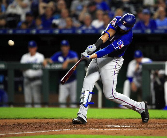 Texas Rangers' Ronald Guzman hits a two-run home run off Kansas City Royals starting pitcher Jorge Lopez (28) during the sixth inning of a baseball game at Kauffman Stadium in Kansas City, Mo., Wednesday, May 15, 2019. (AP Photo/Orlin Wagner)