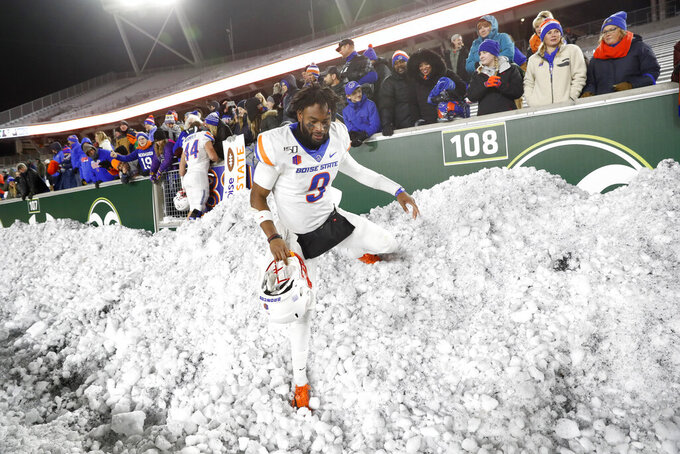 Boise State quarterback Jaylon Henderson scales back down a snowbank after greetings fans following the second half of an NCAA college football game against Colorado State Friday, Nov. 29, 2019, in Fort Collins, Colo. Boise State won 31-24. (AP Photo/David Zalubowski)