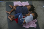 Migrant children sleep on a mattress on the floor of the AMAR migrant shelter in Nuevo Laredo, Mexico, Wednesday, July 17, 2019. Asylum-seekers grappled to understand what a new U.S. policy that all but eliminates refugee claims by Central Americans and many others meant for their bids to find a better life in America amid a chaos of rumors, confusion and fear. (AP Photo/Marco Ugarte)