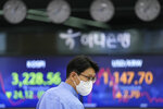 A currency trader walks by the screens showing the Korea Composite Stock Price Index (KOSPI), left, and the foreign exchange rate between U.S. dollar and South Korean won at the foreign exchange dealing room in Seoul, South Korea, Friday, July 9, 2021. Shares were mostly lower in Asia on Friday after stocks pulled back from their recent record highs on Wall Street as bond yields fell and investors turned cautious. (AP Photo/Lee Jin-man)