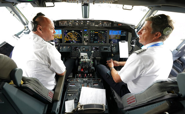 American Airlines pilots captain Pet Gamble, left, and first officer John Konstanzer chat in the cockpit of a Boeing 737 Max jet before taking off from Dallas Fort Worth airport in Grapevine, Texas, Wednesday, Dec. 2, 2020. American Airlines took its long-grounded Boeing 737 Max jets out of storage, updating key flight-control software, and flying the planes in preparation for the first flights with paying passengers later this month.  (AP Photo/LM Otero)