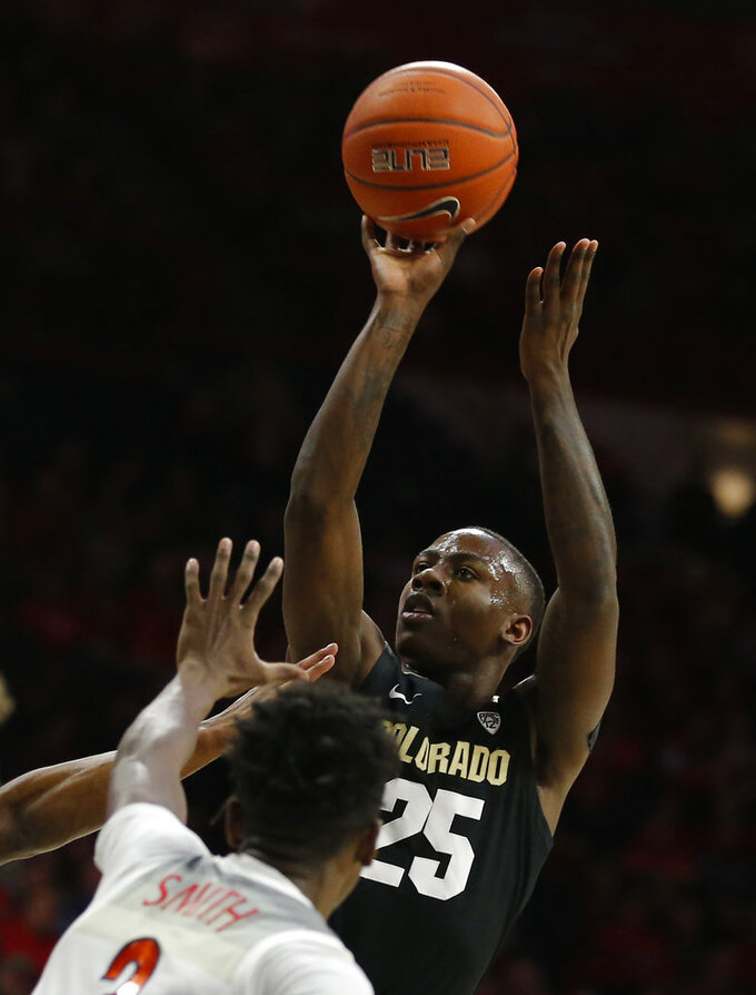 Colorado guard McKinley Wright IV (25) shoots over Arizona guard Dylan Smith in the first half during an NCAA college basketball game, Thursday, Jan. 3, 2019, in Tucson, Ariz. (AP Photo/Rick Scuteri)