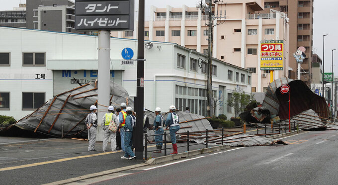 The roofs of a car factory are seen on sidewalk after typhoon hit Fukuoka, southwestern Japan Monday, Sept. 7, 2020. The second powerful typhoon to slam Japan in a week left people injured, damaged buildings, caused blackouts at nearly half a million homes and paralyzed traffic in southern Japanese islands before headed to South Korea.(Kyodo News via AP)