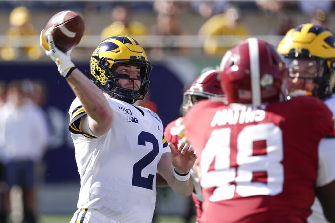 Michigan quarterback Shea Patterson (2) throws a pass as he is pressured by Alabama defensive lineman Phidarian Mathis (48) during the first half of the Citrus Bowl NCAA college football game, Wednesday, Jan. 1, 2020, in Orlando, Fla. (AP Photo/John Raoux)