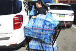 After a break in a 24-inch water main, Alexis Beck, of Castle Shannon, loads her purchase of water into her car, Friday, Sept. 20, 2019, at the Giant Eagle grocery store along Route 88 in Bethel Park, Pa. Beck said that she got water for her family and neighbors She said they were advised to boil what water they got from the tap. A massive water main break in Pittsburgh prompted the rescue of several people and pets, led to school closings and sent a torrent of water careening down streets, looking like river rapids.(Darrell Sapp/Pittsburgh Post-Gazette via AP)