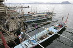 Fishermen check their boats at the lake beside Taal volcano in Talisay, Batangas province, southern Philippines on Friday Jan. 17, 2020. Taal volcano remains life-threatening despite weaker emissions and fewer tremors, an official said Friday and advised thousands of displaced villagers not to return to the danger zone. (AP Photo/Aaron Favila)