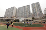 FILE - In this Jan. 28, 2016, file photo, residents exercise at a school near an apartment complex, the former location of the Brothers Home, in Busan, South Korea. A notorious South Korean facility that kidnapped, abused and enslaved children and the disabled for a generation was also shipping children overseas for adoption, part of a massive profit-seeking enterprise that thrived by exploiting those trapped within its walls, The Associated Press has found.(AP Photo/Ahn Young-joon, File)