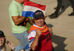 Orange-clad fans flash a thumbs up on their way to watch the first free practice session ahead of Sunday's Formula One Dutch Grand Prix at the Zandvoort racetrack, Netherlands, Friday, Sept. 3, 2021. (AP Photo/Francisco Seco)
