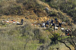 FILE - In this Jan. 27, 2020 file photo, investigators work the scene of a helicopter crash that killed former NBA basketball player Kobe Bryant, his 13-year-old daughter, Gianna, and several others in Calabasas, Calif. Autopsy reports released Friday, May 15, 2020 show that the pilot who flew Bryant show he did not have drugs or alcohol in his system when the helicopter crashed in Southern California in January, killing all nine aboard. (AP Photo/Mark J. Terrill, File)