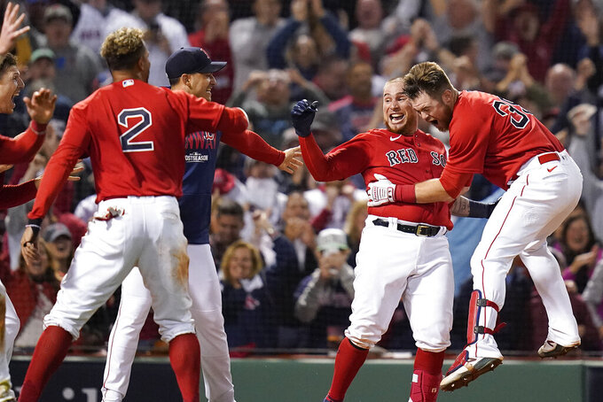 Boston Red Sox catcher Christian Vazquez, center, celebrates with teammates after hitting a two-run walk-off home run during the thirteenth inning against the Tampa Bay Rays during Game 3 of a baseball American League Division Series, Sunday, Oct. 10, 2021, in Boston. The Red Sox won 6-4. (AP Photo/Charles Krupa)