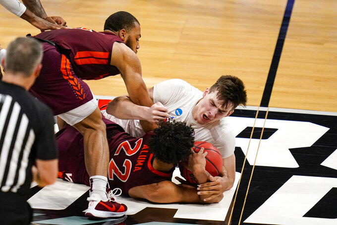 Florida forward Colin Castleton (12), Virginia Tech forward Keve Aluma (22) and forward David N'Guessan (5) go for a loose ball in the first half of a first round game in the NCAA men's college basketball tournament at Hinkle Fieldhouse in Indianapolis, Friday, March 19, 2021. (AP Photo/Michael Conroy)
