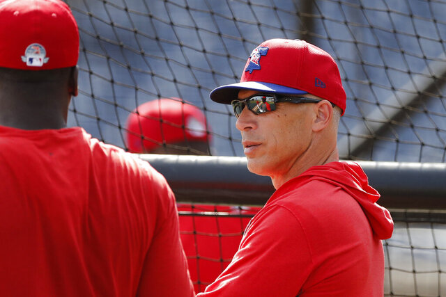 Philadelphia Phillies manager Joe Girardi talks to shortstop Didi Gregorius during pregame of a spring training baseball game, Wednesday, March 4, 2020, in Clearwater, Fla. (AP Photo/Carlos Osorio)