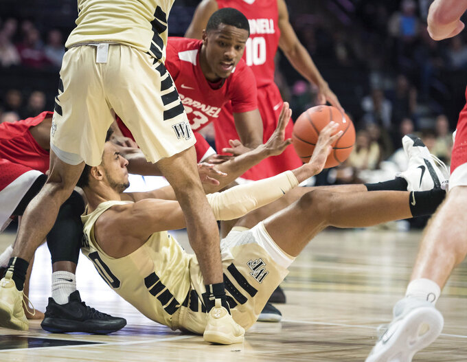Wake Forest center Olivier Sarr (30) passes the ball from the floor after a scramble during the first half of an NCAA college basketball game against Cornell on Wednesday, Jan. 2, 2019, in Winston-Salem, N.C. (Allison Lee Isley/The Winston-Salem Journal via AP)