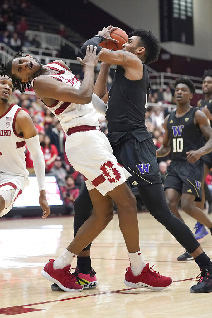 Stanford guard Daejon Davis, center left, reacts after colliding with Washington guard Jamal Bey, center right, during the first half of an NCAA college basketball game Thursday, Jan. 9, 2020, in Stanford, Calif. (AP Photo/Tony Avelar)