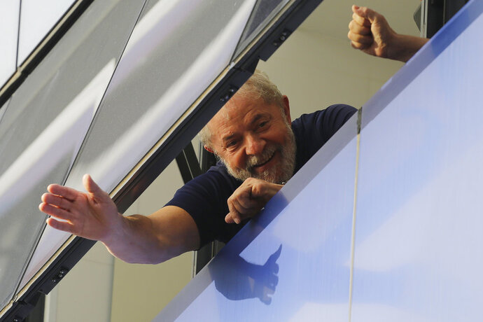 FILE - In this April 7, 2018 file photo, Brazil's former President Luiz Inacio Lula da Silva waves to supporters from a window of the Metal Workers Union headquarters in Sao Bernardo do Campo, Brazil, before he was later jailed for corruption on the same day. Imprisonment has not knocked the former president out of the lead in Brazil's upcoming presidential race. He also leads in all proposed runoff combinations. (AP Photo/Nelson Antoine, File)