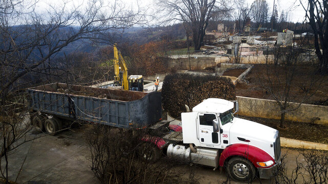 FILE - In this Feb. 8, 2019, file photo, an excavator loads debris onto a truck while clearing a property burned by the Camp Fire in Paradise, Calif. A $13.5 billion settlement covering most of the losses from a series of catastrophic wildfires that drove Pacific Gas and Electric into bankruptcy is turning into a financial tug of war pitting the interests of U.S. taxpayers against the disaster victims still trying to rebuild their lives. (AP Photo/Noah Berger, File)