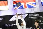 Mercedes driver Lewis Hamilton of Britain celebrates his victory flanked by third place Red Bull driver Max Verstappen of the Netherlands on the podium, after the Emirates Formula One Grand Prix at the Yas Marina racetrack in Abu Dhabi, United Arab Emirates, Sunday, Nov. 25, 2018.(AP Photo/Luca Bruno)