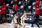 Atlanta Hawks center Clint Capela, middle, heads to the other end of the court after scoring against the Milwaukee Bucks, while injured Hawks guard Trae Young, lower right, and teammates on the bench celebrate during the second half of Game 4 of the NBA basketball Eastern Conference finals Tuesday, June 29, 2021, in Atlanta. (AP Photo/Brynn Anderson)