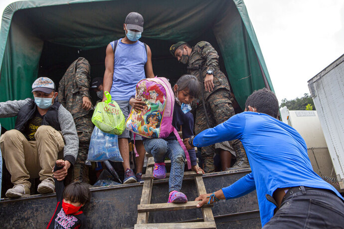 A Honduran migrant child is helped off a Guatemalan army truck after being returned to El Florido, Guatemala, one of the border points between Guatemala and Honduras, Tuesday, Jan. 19, 2021. A once large caravan of Honduran migrants that pushed its way into Guatemala last week had dissipated by Tuesday in the face of Guatemalan security forces. (AP Photo/Oliver de Ros)