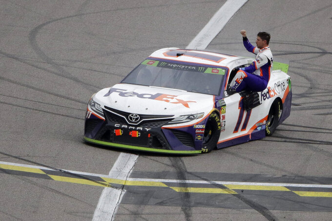 Denny Hamlin celebrates after winning a NASCAR Cup Series auto race at Kansas Speedway in Kansas City, Kan. Sunday, Oct. 20, 2019. (AP Photo/Charlie Riedel)