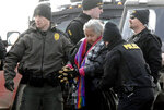 FILE - In this Feb. 23, 2017, file photo, an elderly woman is escorted to a transport van after being arrested by law enforcement at the Oceti Sakowin camp as part of the final sweep of the Dakota Access pipeline protesters in Morton County near Cannon Ball, N.D. Protests and lawsuits against major oil and gas pipeline projects have slowed or stalled projects across the U.S. (Mike McCleary/The Bismarck Tribune via AP, Pool, File)