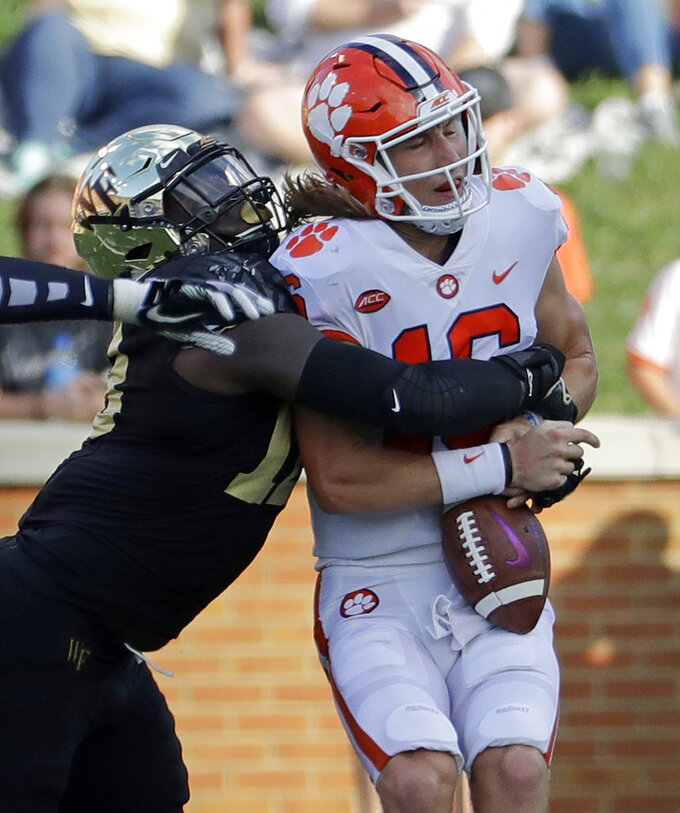 Clemson's Trevor Lawrence (16) is sacked by Wake Forest's Carlos Basham Jr. (18) during the first half of an NCAA college football game in Charlotte, N.C., Saturday, Oct. 6, 2018. (AP Photo/Chuck Burton)