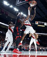Toronto Raptors forward Chris Boucher, top, dunks over Portland Trail Blazers guard Kent Bazemore during the first half of an NBA basketball game in Portland, Ore., Wednesday, Nov. 13, 2019. (AP Photo/Craig Mitchelldyer)
