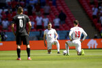 England's Mason Mount, right, and Declan Rice take the knee pair to the kick-off of the Euro 2020 soccer championship group D match between England and Croatia, at Wembley stadium, London, Sunday, June 13, 2021. (Laurence Griffiths, Pool via AP)